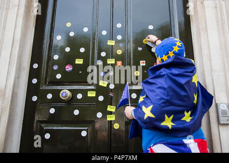 London, UK. 23 June 2018. A protester puts stickers on the front door of the Cabinet Office. Remain supporters and protesters at an Anti-Brexit march and rally for a People's Vote. Photo: Bettina Strenske/Alamy Live News - Stock Image
