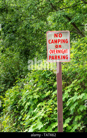 No camping or overnight parking warning sign on post with red lettering on rural road beside green trees. - Stock Image