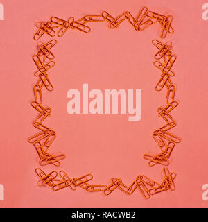 Orange paper clip frame over coral color paper background with free space for text. Image shot from above. - Stock Image