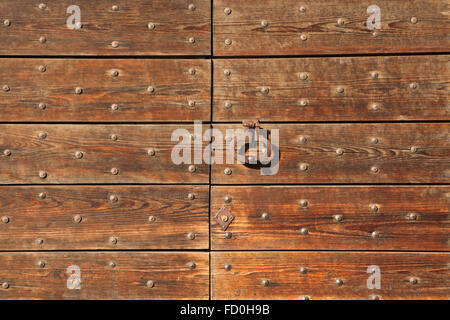 Old metal doorknocker on the wooden gate fixed with rivets in Bergamo, Lombardy, Italy. - Stock Image