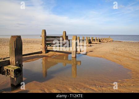 A breakwater at low tide with pool reflection on a North Norfolk beach at Bacton-on-Sea, Norfolk, England, United Kingdom, Europe. - Stock Image