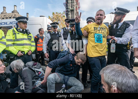 London, UK. 31st October 2018.  Most people at Extinction Rebellion's Declaration of Rebellion left the road they were blocking in front of parliament after a closing address by George Monbiot, but several small groups decided to remain on the road, including Donnachadh McCarthy and George Monbiot. Police immediately warned them they would be arrested if they did not move. Police arrest  two more protesters. By the time I left around 15 arrests had been made while some others agreed to leave the road. Peter Marshall/Alamy Live News - Stock Image