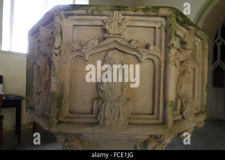 Detail from the 15th century stone font with carvings of the apostles, St Peter, St Nicholas Church, Buckenaham - Stock Image