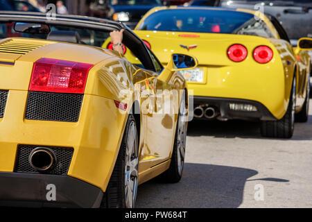 Miami Beach Florida Ocean Drive car auto vehicle yellow sports car Corvette Lamborghini convertible rear view traffic cruising - Stock Image