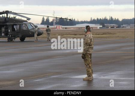 A U.S. Army Soldier assigned to 2-158th Assault Helicopter Battalion, 16th Combat Aviation Brigade, 7th Infantry Division watches as a flight crew prepares a UH-60 Black Hawk to depart from Joint Base Lewis-McChord, Wash., for the National Training Center Jan. 9, 2016. The Soldiers and aircraft will participate in training with other units from 7th Infantry Division to prepare for future missions. (U.S. Army photo by Capt. Brian Harris/Released) - Stock Image