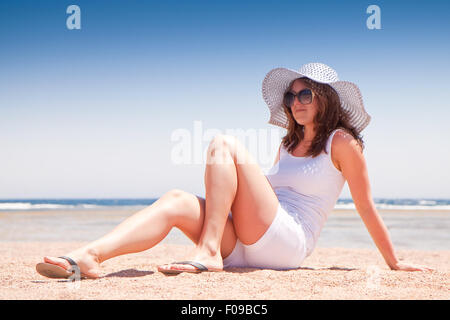 Young girl sitting on the sand at the beach - Stock Image