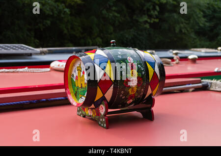 Wooden barrel, decorated in traditional canal art, on top of a narrowboat, Stoke Bruerne, UK - Stock Image