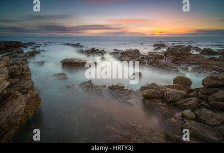 Rocky beach sunset - Stock Image