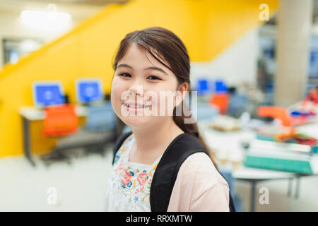 Portrait confident junior high girl student in library - Stock Image