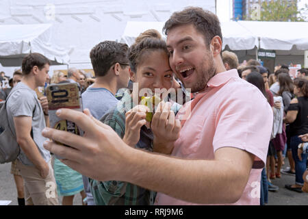 An attractive couple pose with their pickles at the annual Pickle Day celebration on Orchard Street on the Lower East Side of Manhattan. - Stock Image