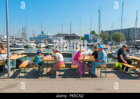 View of people on a summer afternoon eating lunch at tables at the Kalamaja Sunday Market in Tallinn harbor, Estonia. - Stock Image