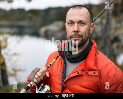 Portrait of man with fishing rod - Stock Image