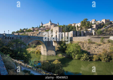 Shot from green water river Tagus, Tajo in Spanish, of Alcantara arch bridge and door,  landmark and monument from ancient Roman age, in Toledo city,  - Stock Image