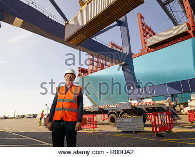 Dock worker by cargo container and truck at Port of Felixstowe, England - Stock Image
