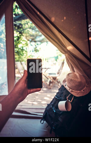 vertical view of a hand of a hiker person resting while consulting the phone in a camping tent, travel discovery concept, point of view shot - Stock Image