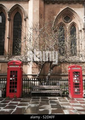 Two red telephone boxes next to a church - Stock Image