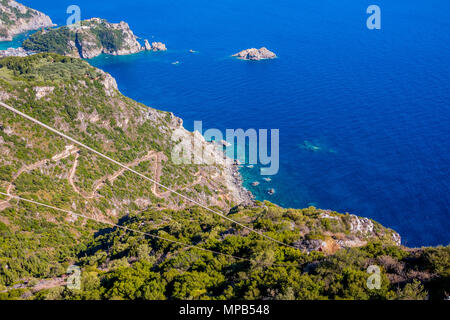 serpentine road in mountains covered with forest. Amazing View from drone, Corfu island, Greece. Clear blue water. Aerial photo.amazing view on ionian sea.Palaiokastritsa bay - Stock Image