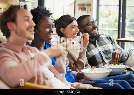 Smiling couples watching movie, eating popcorn - Stock Image