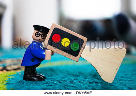 Poznan, Poland - February 9, 2019: Plastic toy man figure in uniform and glasses holding up a wooden traffic light with green, yellow and red lamps in - Stock Image