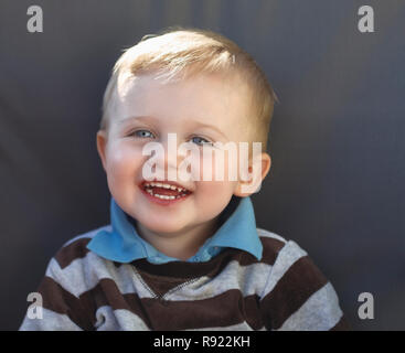 Head and shoulder portrait of happy young caucasian toddler child with big smile, laughing with open mouth - Stock Image