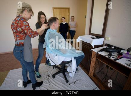 International Space Station Expedition 59 crew member Nick Hague of NASA has his hair cut by a stylist as fellow crew member, Christina Koch of NASA, center, assists at the Baikonur Cosmodrome March 12, 2019 in Baikonur, Kazakhstan. Expedition 59 crew: Christina Koch of NASA, Alexey Ovchinin of Roscosmos, and Nick Hague of NASA will launch March 14th onboard the Soyuz MS-12 spacecraft for a six-and-a-half month mission on the International Space Station. - Stock Image