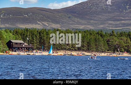 Loch Morlich and Cairngorms in Glenmore Cairngorms National Park Highland Scotland with the east beach full of visitors and boats - Stock Image