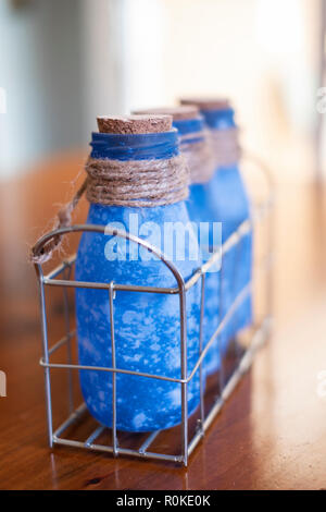 Three blue bottles with corks, tied with sisal hemp twine in a wire container. - Stock Image