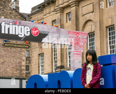 Edinburgh, Scotland, UK. 14th August 2018. Edinburgh Fringe Festival, Royal Mile, Edinburgh, Scotland, United Kingdom. A young Asian girl watches a street performance - Stock Image
