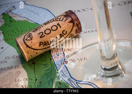 Pauillac Bordeaux French wine tour tasting concept, with wine glass, 2001 Pauillac cork in close up, on old historic Bordeaux wine areas map - Stock Image