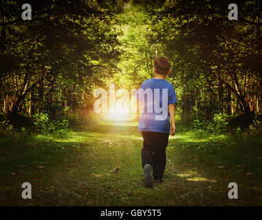 A child is walking in the dark woods into a bright light on a path for a freedom or happiness concept. - Stock Image