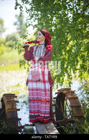 Attractive woman in scarf and traditional russian clothes stands on a small pier near the lake, looks right, posing for a photo, vertical view - Stock Image