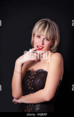 Attractive blond woman posing on studio dark background - Stock Image