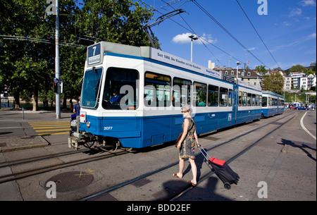 Woman looking for passing Trams before crossing the street Zurich Switzerland - Stock Image