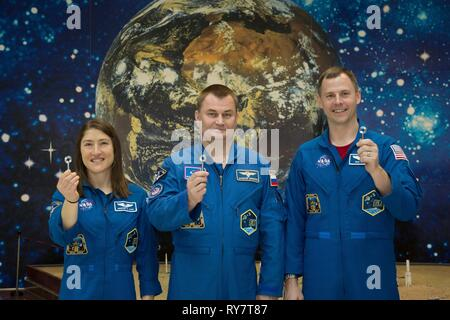 International Space Station Expedition 59 crew members Nick Hague of NASA (right), Christina Koch of NASA (left) and Alexey Ovchinin of Roscosmos (center) pose with copies of the Launch Key at the Baikonur Cosmodrome March 12, 2019 in Baikonur, Kazakhstan. Expedition 59 crew: Christina Koch of NASA, Alexey Ovchinin of Roscosmos, and Nick Hague of NASA will launch March 14th onboard the Soyuz MS-12 spacecraft for a six-and-a-half month mission on the International Space Station. - Stock Image