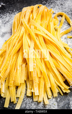 Yellow egg homemade raw tagliatelle pasta. Dark marble background with flour. - Stock Image