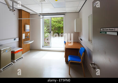 Unoccupied clinic examination room with sign on door - Stock Image