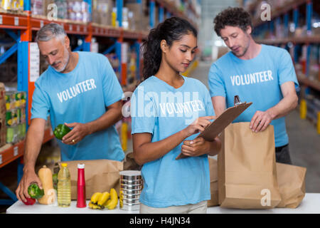 Three volunteers packing eatables in cardboard box in a warehouse - Stock Image