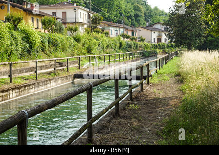 An irrigation canal wends its way through italy farmland - Stock Image