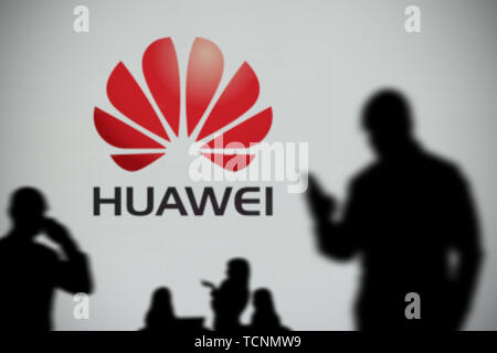 The Huawei logo is seen on an LED screen in the background while a silhouetted person uses a smartphone in the foreground (Editorial use only) - Stock Image