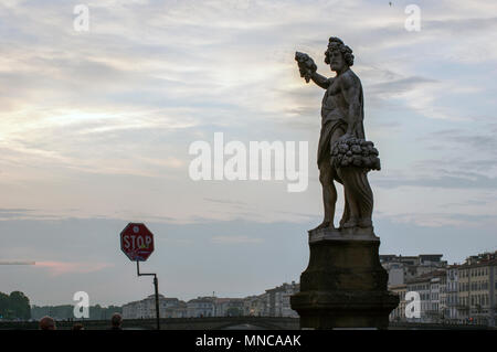 silhouetted statue at the end of the ponte vecchio in florence italy with hazy cloudy skies - Stock Image