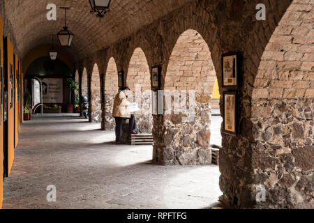 A man reads a newspaper along the colonnade of the San Francisco Convent in the Plaza de Aranzazu in the state capital of San Luis Potosi, Mexico. The chapel and convent was built between 1749 and 1760 and features Churrigueresque details and tiled domes. - Stock Image