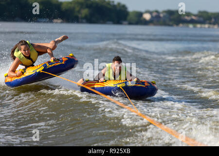 Young man and woman tubing together on Fox River in summer, De Pere, Wisconsin, USA - Stock Image