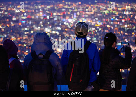 People in focus in the foreground watching cityscape of Sapporo with city lights at night, out-of-focus. In Sapporo, Hokkaido, Japan. - Stock Image