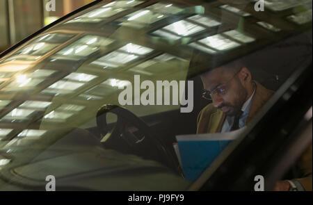 Businessman reviewing paperwork in car at night - Stock Image