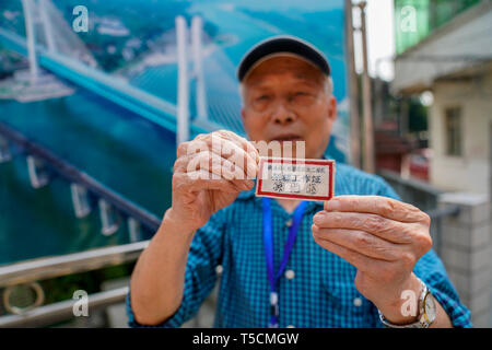 (190423) -- CHONGQING, April 23, 2019 (Xinhua) -- Sun Yisun, a former builder of the previous Baishatuo Yangtze River railway bridge, shows his old employee's card in Jiangjin of southwest China's Chongqing Municipality, April 23, 2019. The previous Baishatuo Yangtze River railway bridge, completed in 1959, will stop service after April 24. All trains will run on the new double decker steel truss cable stay railway bridge after that day. The new bridge has 4 tracks on the upper deck for passenger trains with a designed speed of 200 kilometers per hour and 2 tracks on the lower deck for cargo t - Stock Image