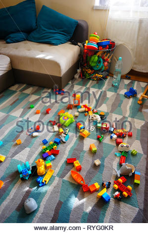 Poznan, Poland - March 2, 2019: Messy living room with Lego Duplo blocks laying around on a carpet floor. - Stock Image