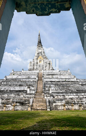 Large white ancient pagoda looking through the door frame of Wat Phu Khao Thong temple is famous tourist attraction - Stock Image