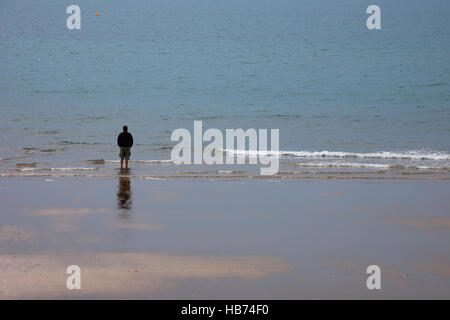 Solitary man wearing shorts standing on the edge of a beach looking out to sea - Stock Image