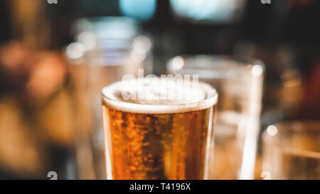 Close up of a pint of beer and empty glasses on a table - Stock Image
