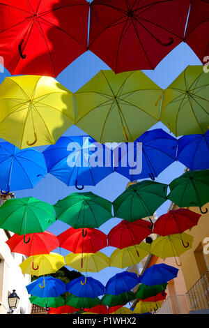 Colourful Umbrellas over streets in Spanish Village during Fiesta - Stock Image